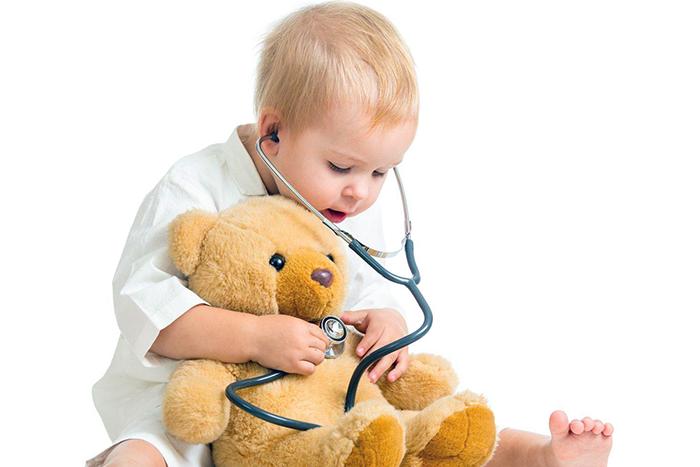 En una foto a color se ve un niño comprobando el corazón de un osito de peluche con un estetoscopio