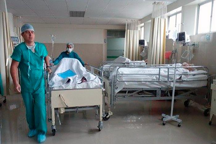 En una foto a color donde se ve como un doctor entra a una habitación con una camilla