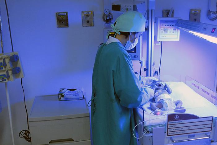 Foto de enfermera en cuidados intensivos con un neonato